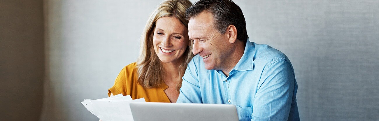 A happy couple reviews their dental invoices.