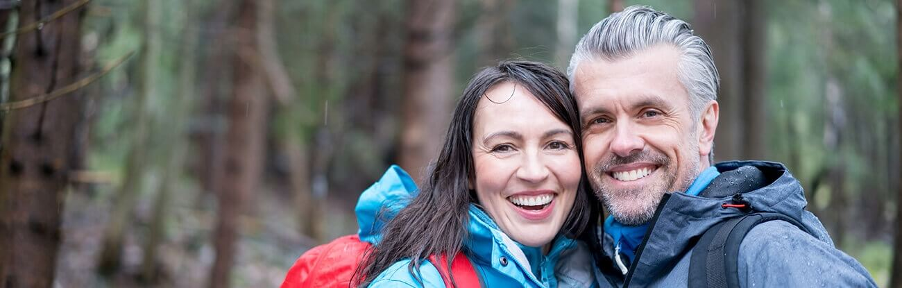 A married couple with healthy teeth on a hike.