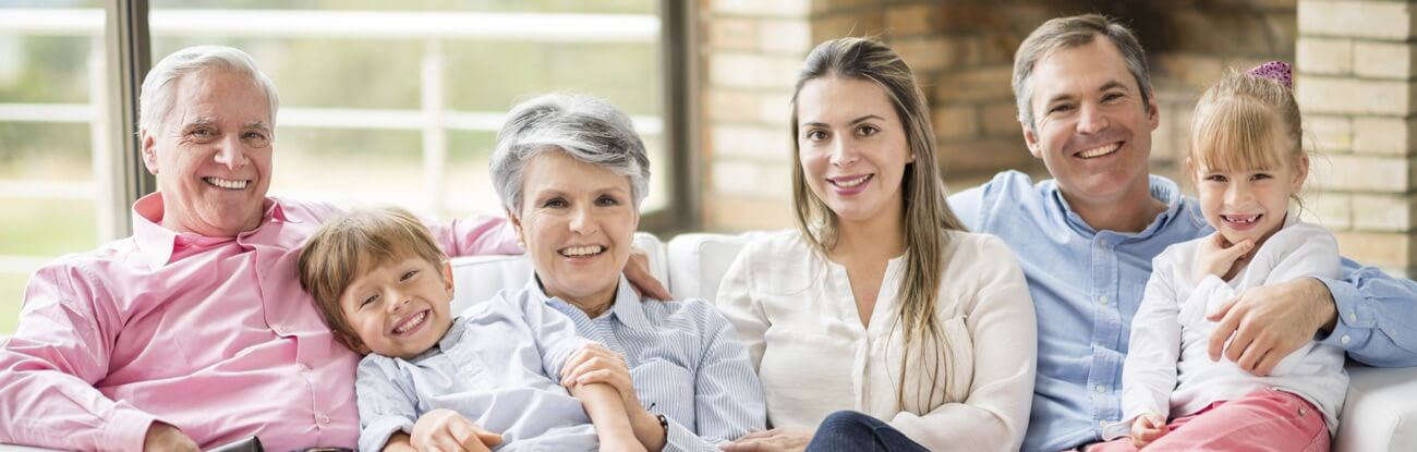 Multi-generational family smiles as they sit in their living room on the couch.