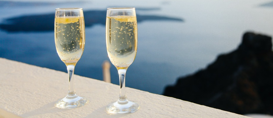 Two delicate stemmed champagne glasses perch on a railing overlooking a seascape