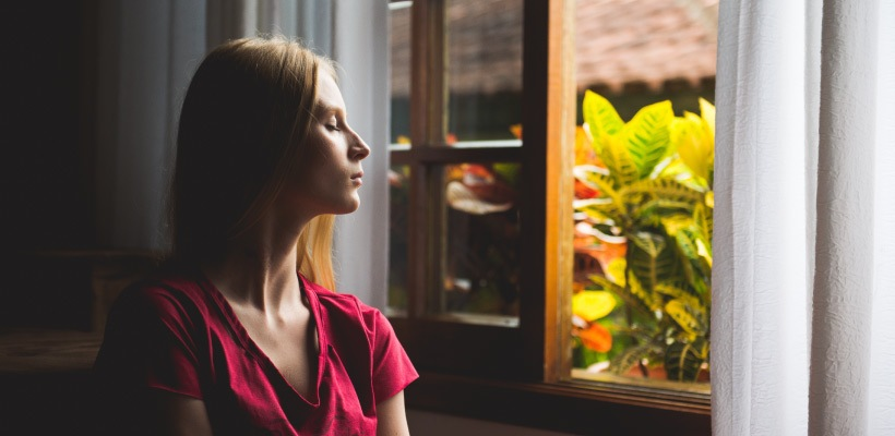 Pain-free blonde woman after root canal therapy relaxes and breathes deeply by an open window in a magenta shirt