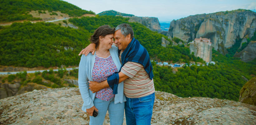 A middle-aged husband and wife embrace on an picturesque overlook in the hillsides of Greece