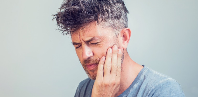 Middle-aged man wearing a gray shirt touches his cheek with his eyes closed due to sensitivity and pain from a loose filling
