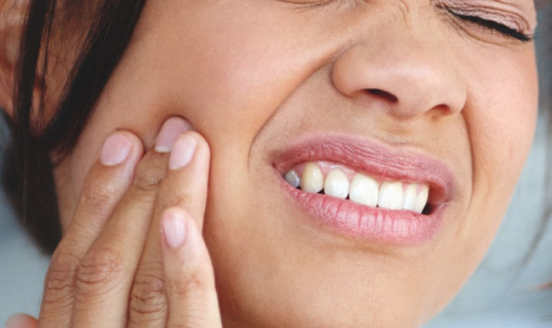 woman holding her cheek with tooth pain requiring a tooth extraction