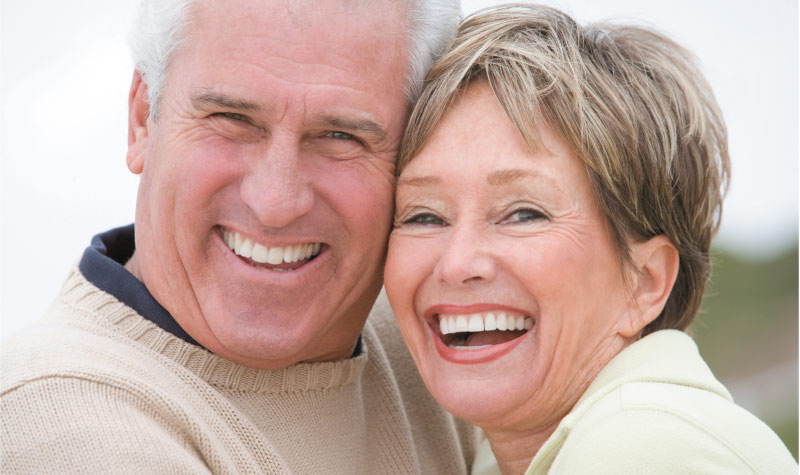 senior couple smiling and laughing after learning about same day crowns