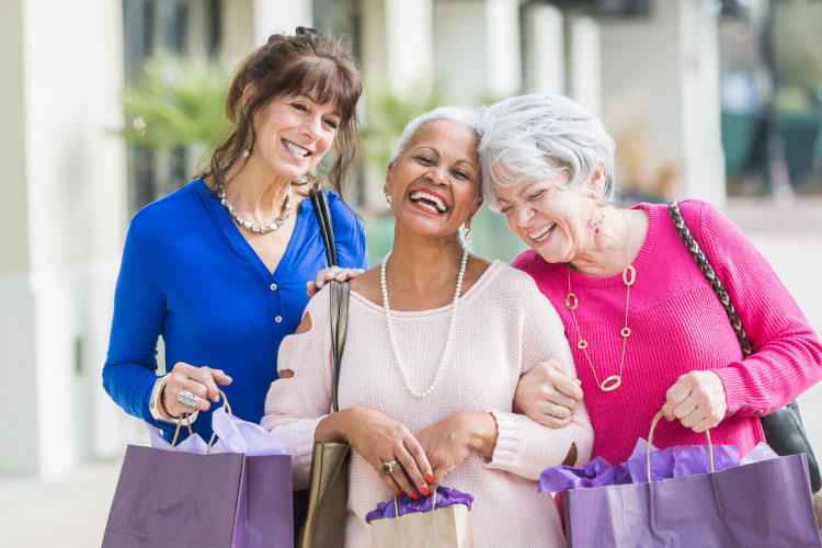 Three mature ladies laughing with arms linked carrying shopping bags