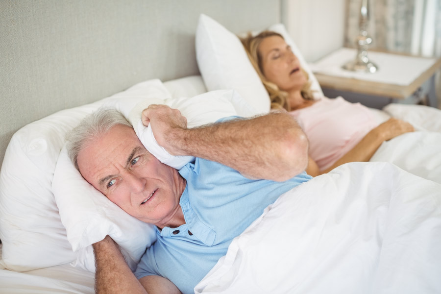 Man with a pillow over his ears while his wife snores loudly due to sleep apnea