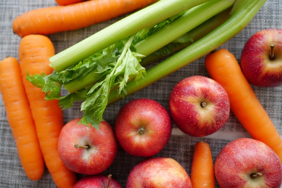 Carrots, celery and apples on a tabletop